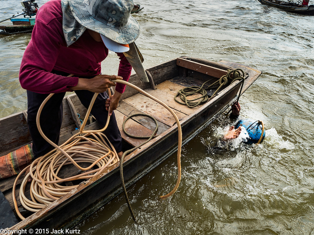14 OCTOBER 2015 - BANGKOK, THAILAND: A diver, wearing a home made dive helmet, surfaces from the bottom of the Chao Phraya River in Bangkok. Divers work in two man teams on small boats in the Chao Phraya River. One person stays in the boat while the diver scours the river bottom for anything that can be salvaged and resold. The divers usually work close to shore because the center of the river is a busy commercial waterway with passenger boats and commercial freight barges passing up and down the river all day long. The Chao Phraya is a dangerous river to dive in. It's deep, has large tidal fluctuations, is fast flowing and badly polluted. The divers make money only when they sell something.    PHOTO BY JACK KURTZ