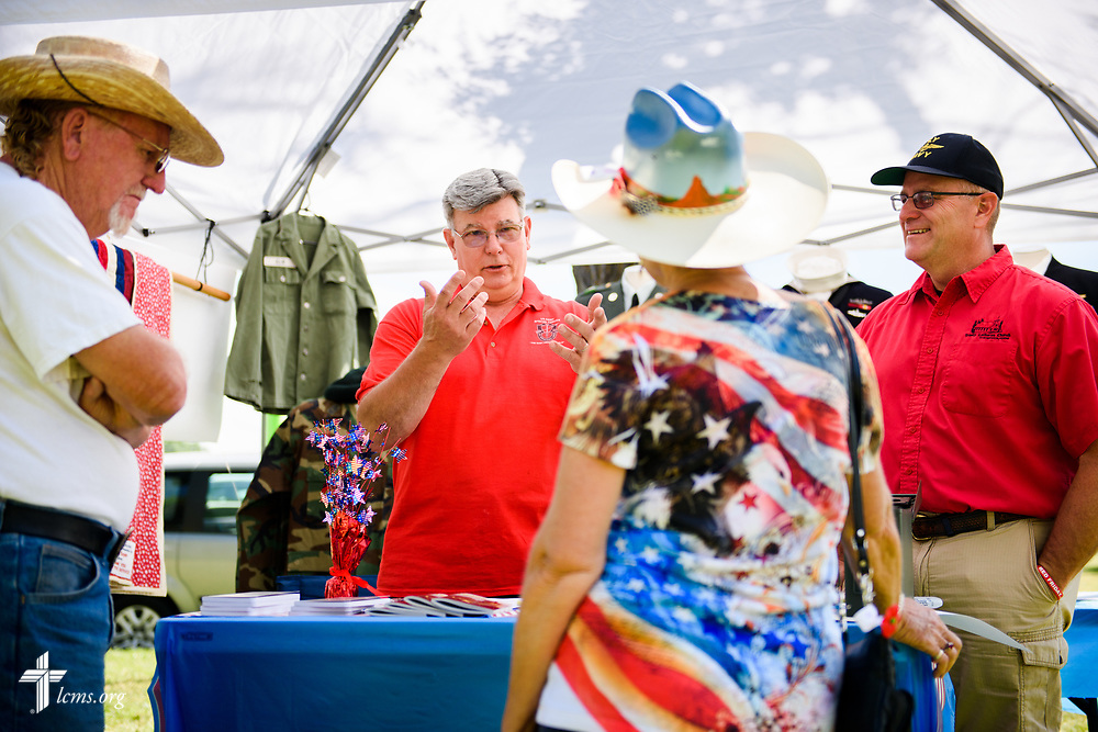 Paul Turpin (center, left), a veteran and church member at Trinity Lutheran Church, Grangeville, Idaho, and the Rev. Michael Musegades, a fellow veteran and the pastor of the church, chat with visitors Tom Voyles and Mary Jane Finlay of Texas in the TLC4Vets outreach tent at the Grangeville Border Days Independence Day celebration and parade on Tuesday, July 4, 2017, in Grangeville. LCMS Communications/Erik M. Lunsford