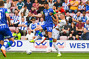 Leeds United defender Ben White (5) and Wigan Athletic forward Kieffer Moore (19) in action during the EFL Sky Bet Championship match between Wigan Athletic and Leeds United at the DW Stadium, Wigan, England on 17 August 2019.