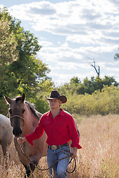 rugged All American cowboy with horse in a field