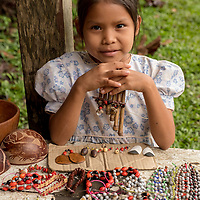 A local Peruvian girl sells handicrafts such as bead necklaces and wooden flutes at her stand in Casual off of the Marañon River. Pacaya Samiria National Reserve, Upper Amazon, Peru.