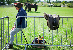 © Licensed to London News Pictures.29/07/15<br /> Borrowby, UK. <br /> <br /> A woman sits on a shooting stick and watches the events at the Borrowby Country Show and Gymkhana in North Yorkshire.<br /> <br /> Photo credit : Ian Forsyth/LNP
