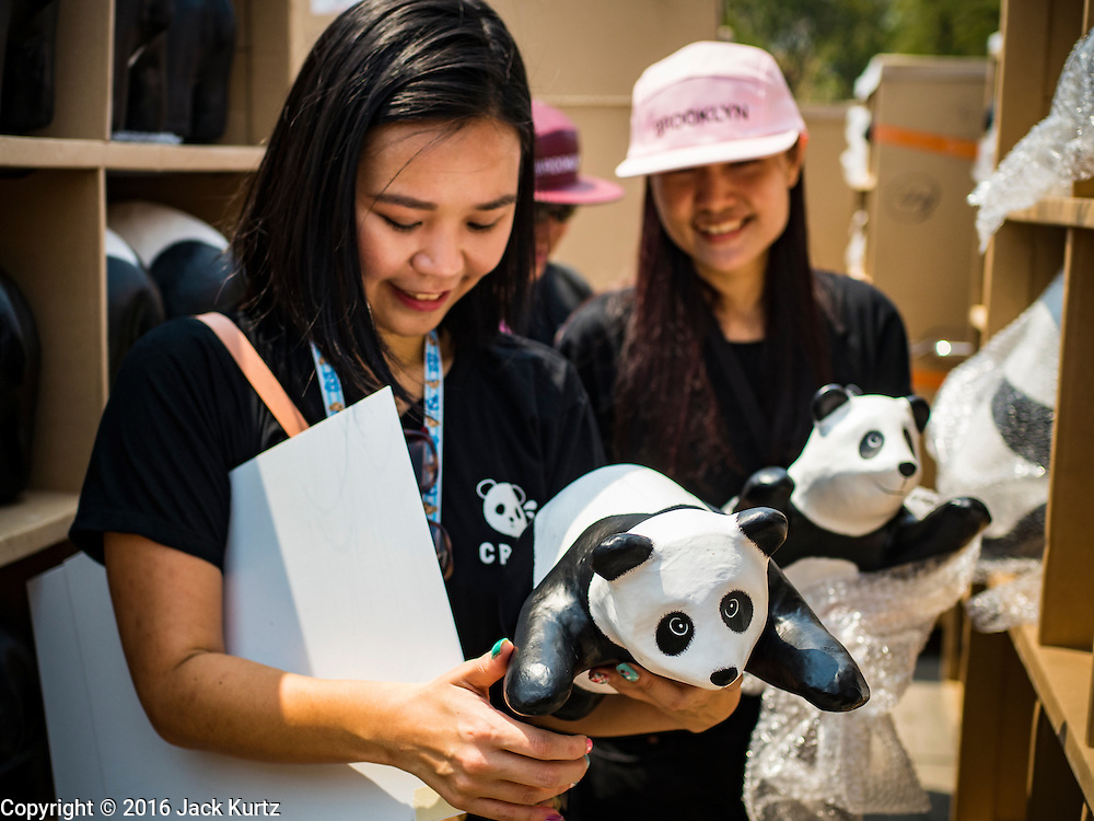 """04 MARCH 2016 - BANGKOK, THAILAND: Volunteers hold paper maché pandas before setting them out for the """"1600 Pandas+ World Tour in Thailand: For the World We Live In and the Ones We Love"""" exhibit Friday at Sanam Luang in Bangkok. The 1600 paper maché pandas, an art installation by French artist Paulo Grangeon will travel across Bangkok and parts of central Thailand for the next week and then will be displayed at Central Embassy, a Bangkok shopping mall, until April 10. The display of pandas in Thailand is benefitting World Wide Fund for Nature - Thailand and is sponsored by Central Embassy with assistance from the Tourism Authority of Thailand and Bangkok Metropolitan Administration and curated by AllRightsReserved Ltd.     PHOTO BY JACK KURTZ"""