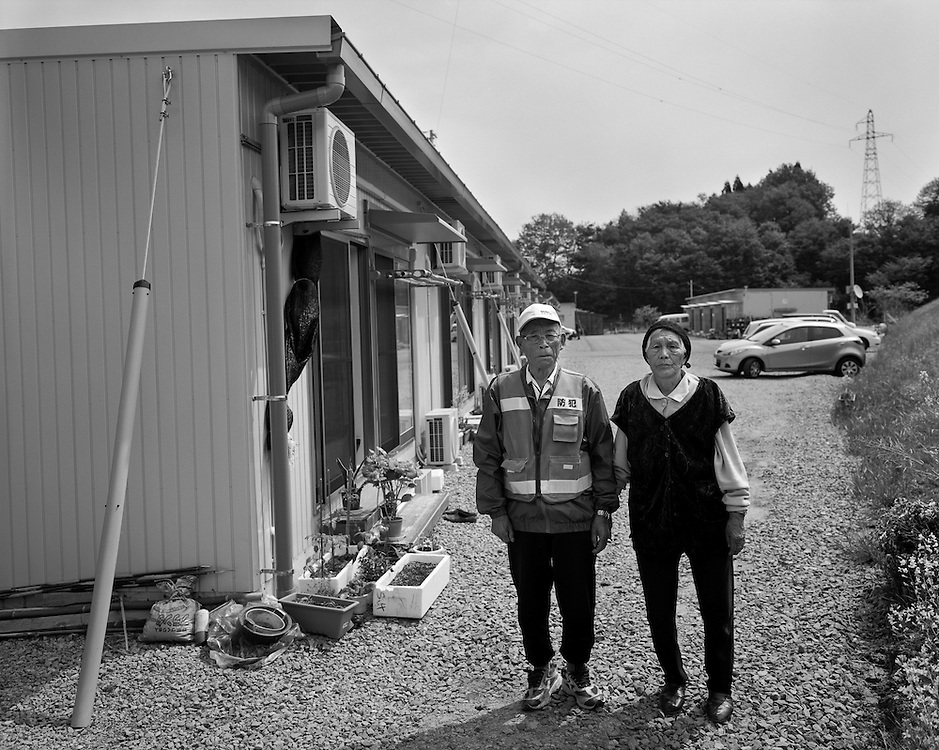 Mr. and Mrs  Takano standing next to the temporary housing in  Fukushima City, about  30 km  from their  home in the  contaminated  farming community of Iitate,Fukushima.