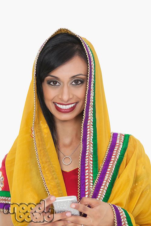 Portrait of an attractive Indian female in traditional wear holding cell phone over gray background