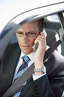 Businessman using mobile phone in car elevated view
