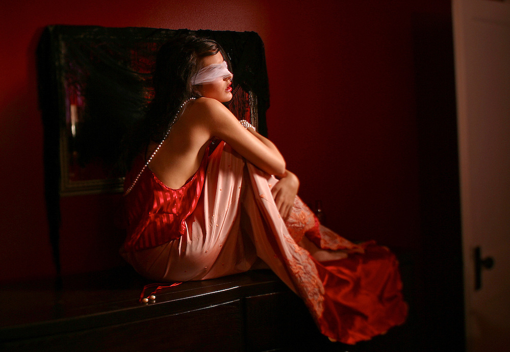 Blinded folded young woman in a red dress sitting on a dresser in a red room