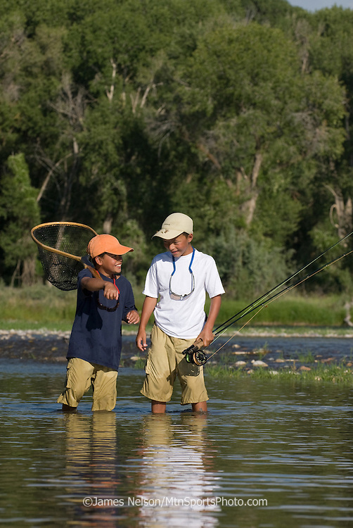 Eight- and 10-year-old brothers walk to a favorite spot to fish for trout on the South Fork of the Snake River, Idaho.