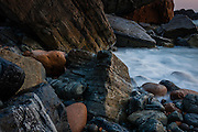 The colorful rocks and pebbles of Grota Beach, in Sintra-Cascais Natural Park, are probably the most beautiful rocks in the coast near Lisbon.