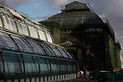 Glasshouses, 19th and 20th centuries, Museum National d'Histoire Naturelle, Jardin des Plantes, Paris, France. Low angle view showing, left to right, incubators, restored 1995-97, by Paul Chemetov and Borja Huidobro, Plant History Glasshouse (formerly Australian Glasshouse), 1830s, Rohault de Fleury, New Caledonia Glasshouse (formerly The Mexican Hothouse), 1830s, Charles Rohault de Fleury, Tropical Rainforest Glasshouse (formerly Le Jardin d'Hiver or Winter Gardens), 1936, René Berger. A workman is restoring a door in the passageway between the incubator and the Plant History Glasshouse.