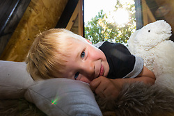 Dad of two Tom Prior has created a beautiful shingle clad, two floor play house in the garden of his Shoreham, West Sussex home for his children. Tom's son Jackson, 4, snuggle up in the upper floor of his playhouse. Shoreham, West Sussex, July 15 2019.