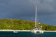 Going to shore in a dinghy from a catamaran sailboat moored in Saltpond Bay, Virgin Islands National Park, St. John, U.S. Virgin Islands.