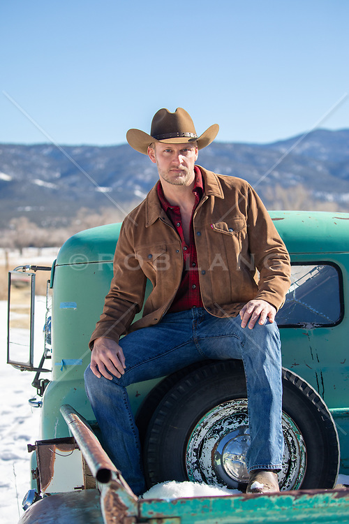 cowboy sitting on the back of a pick up truck