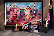 Lady smoker and roadworks signs below an Oasis fashion poster featuring a young woman in a utopian fantasy about to cross a road.