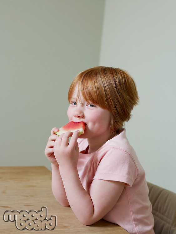 7-8 year old girl smiles as she eats a piece of melon