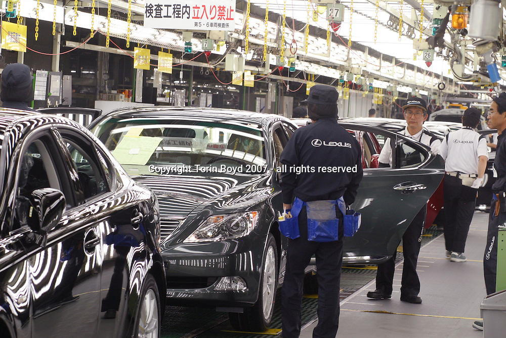 This is the assembly line of Toyota Motor Corporation's Tahara plant located in Aichi Prefecture where Toyota manufactures its luxury Lexus sedans. Many of the cars in this photo are hybrid Lexus models. The models manufactured here include the Lexus models: LS600h (hybrid launched in Japan in May 2007), the 600hl, LS460, 460L, GS450h, 430, 350, 300, IS350 and 250. On average there are 670 vehicles manufactured here every day, which is about one car every 83 seconds coming off the line. Also unique to this plant is the rigid quality control standards that checks for scratches, imperfections, noise levels in the cab, and an extra inspection for blemishes on 36 spots using a hand held digital measuring device that takes 15 to 20 minutes for each car.