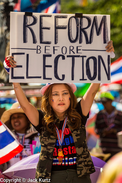 "13 JANUARY 2014 - BANGKOK, THAILAND:  An anti-government protestor holds up a sign calling for political reform during a rally in front of MBK shopping center in Bangkok. Tens of thousands of Thai anti-government protestors took to the streets of Bangkok Monday to shut down the Thai capitol. The protest was called ""Shutdown Bangkok"" and is expected to last at least a week. The Shutdown Bangkok protest is a continuation of protests that started in early November. There have been shootings almost every night at different protests sites around Bangkok, including two Sunday night, but the protests Monday were peaceful. The malls in Bangkok stayed open Monday but many other businesses closed for the day and mass transit was swamped with both protestors and people who had to use mass transit because the roads were blocked.   PHOTO BY JACK KURTZ"