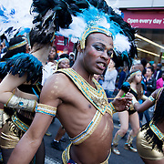 Hackney carnival 2014. The procession started in Ridley Road and passed by the The Hackney Town Hall with thousands of spectators lining the road. A male dancers wearing white,black and blue feathers poses with a stare.
