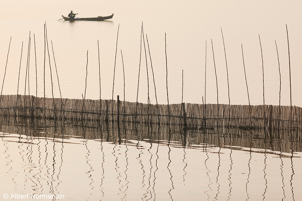 Fishing boat with bamboo fencing and reeds reflected from U Bein Bridge