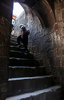 People walking up a steep stone stairway in Shaniwar Wada, Pune, Maharashtra, India.
