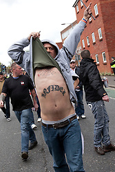 "© Licensed to London News Pictures. 05/05/2012. Luton, UK. A man with ""INFIDEL"" tattooed across his chest. The EDL hold a march and demonstration in Luton town centre. About 1500 EDL supporters attended and about 1200 police. A counter protest was also held. Photo credit : Joel Goodman/LNP"