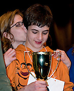MOM'S A FAN--Sam Osheroff gets a kiss from his mother, Nicole Pilevsky, as he admireshis 2011 Howard County Spelling Bee cup, which he now can add.to his collection.  Sam also won the 2010 spelling bee.