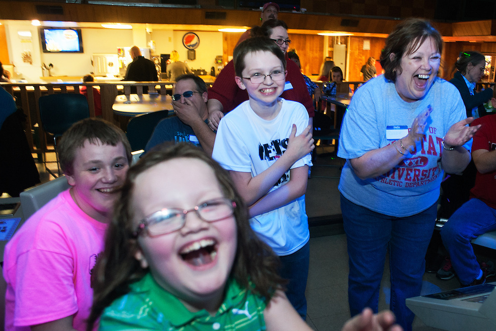 From left to right: Joel Greer, Rhonnie Greer, Randy Greer and Debbie Greer laugh as they watch friends bowl during the bowling party held for Contestants in the Scripps Spelling Bee. Photo by: Ross Brinkerhoff.