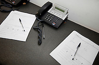 Documents and landline telephones on table