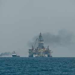 A controlled burn is seen in the distance behind the Seadrill (SDRL) a ultra-deepwater semi-submersible rig West Sirius assigned by Devon Energy (DVN) and Seadrill (SDRL) to operate for BP (BP Plc) is seen near the source of the BP Plc Deep Water Horizon oil spill site in the Gulf of Mexico off the coast of Louisiana, U.S., on Thursday, July 15, 2010. Photographer: Derick E. Hingle/Bloomberg