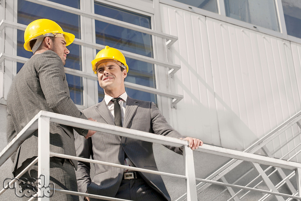 Low angle view of young male architect with coworker discussing on stairway