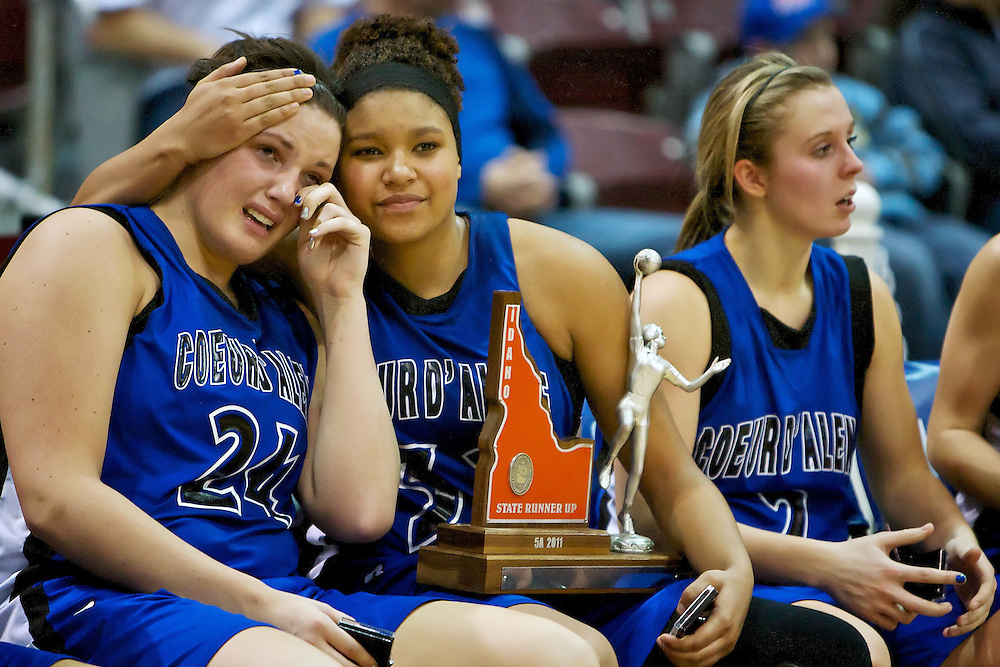 Coeur d'Alene High's Kendalyn Brainard comforts her teammate Carli Rosenthal while sitting next to Heather Baughman, right, after they were presented the 5A state runner up championship trophy Saturday after their 43-39 loss to Lewiston High in the  at the Idaho Center in Nampa.