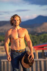 muscular shirtless cowboy outdoors on a ranch at sunset