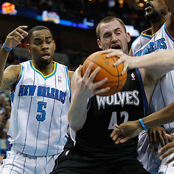 February 7, 2011; New Orleans, LA, USA; Minnesota Timberwolves power forward Kevin Love (42) controls the ball as New Orleans Hornets center D.J. Mbenga (28) and guard Marcus Thornton (5) defend the play during the third quarter at the New Orleans Arena. The Timberwolves defeated the Hornets 104-92.  Mandatory Credit: Derick E. Hingle
