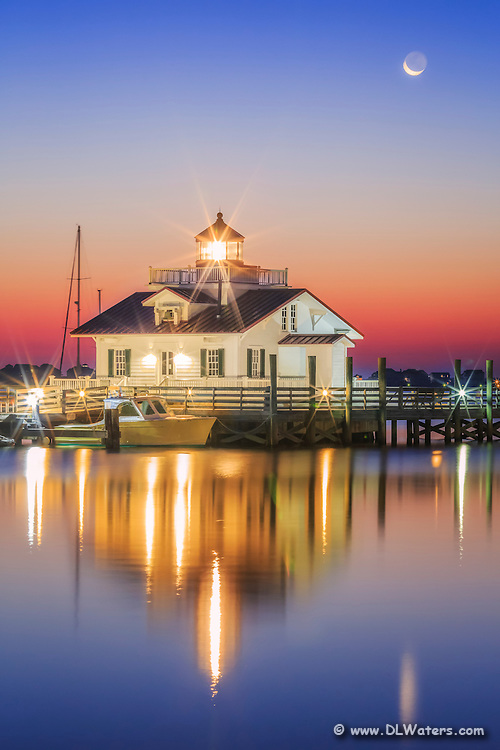 Roanoke Marshes Lighthouse in Manteo North Carolina with the moon setting behind it.   The sun is just brightening the sky and reflecting in the calm waters of Shallowbag Bay.