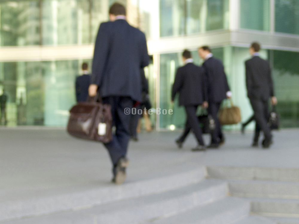 business men walking towards there office building blurry