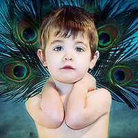 A young boy looking at the camera wearing a peacock feather crown