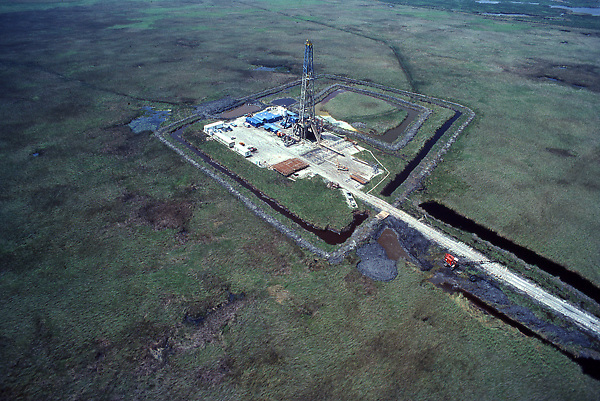 Stock photo of an aerial view of an on-shore rig in a grassy area