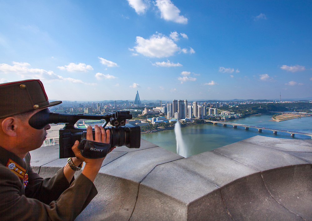Soldier filming Pyongyang City from the Juche Tower in Pyongyang, North Korea.