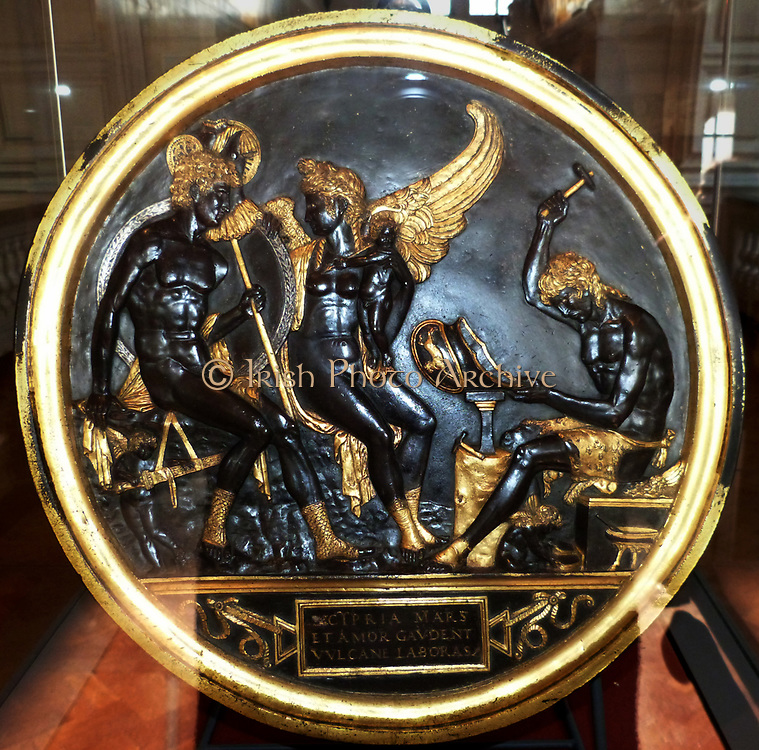Mars, Venus, Cupid and Vulcan c. 1480-1500.  Mars, god of war, sits with his trophies around gazing at his lover Venus, while her cuckolded husband Vulcan fashions a helmet.  This decorated roundel was made in the circle of the Gonzaga court sculptor Antico at Mantua, possibly by the goldsmith Gian Marco Cavalli.