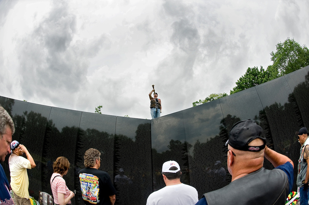 A member of Rolling Thunder poses with a bugle at the apex of the Vietnam Veteran's Memorial in Washington, D.C., as Taps is played over a loudspeaker as part of their motorcycle remembrance ride in Washington D.C. on Sunday May 24, 2009.