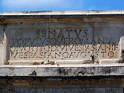 Latin Inscription detail from The Arch of Constantine, a triumphal, or victory arch in Rome. It is positioned between the Collosseum and the Palatine Hill. It commemorates Emperor Constantine's victory in the Battle of Milvian Bridge in the early 4th century AD. It was dedicated in 315 AD and features reliefs/friezes documenting previous Emperors and victory figures.