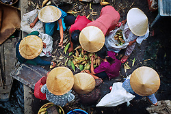 Women sell corn at the vegetable market in the Mekong Delta.