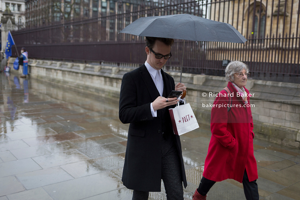 A man checks messages while carrying his Pret a Manger takeaway lunch hooked on his umbrella, in Parliament Square, Westminster, on 30th January 2020, in London, England.
