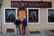 Tourists inspect the menus outside a restaurant in the Slovenian capital, Ljubljana, on 27th June 2018, in Ljubljana, Slovenia.