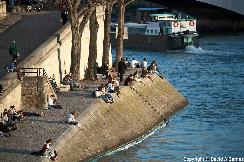 People sunning on banks of Seine, Paris, France