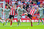 Andy Cannon (#14) of Portsmouth FC tries to run between Max Power (#6) and Grant Leadbitter (#23) of Sunderland AFC during the EFL Sky Bet League 1 match between Sunderland and Portsmouth at the Stadium Of Light, Sunderland, England on 17 August 2019.