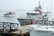 A tour boat, a Coast Guard patrol boat, and a lobster boat cross paths on a foggy day at the Bar Harbor Town Pier.