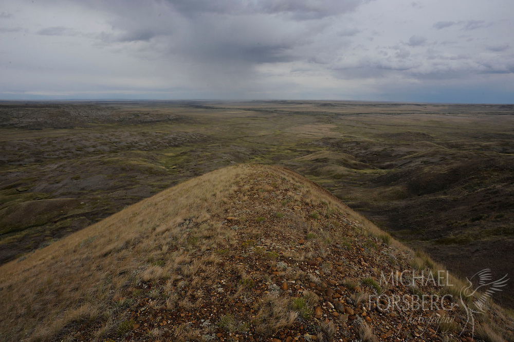 Eye level with a small rain squall, the land falls away to a sweeping vista from top of 70 Mile Butte.  Grasslands National Park, Saskatchewan, Canada.