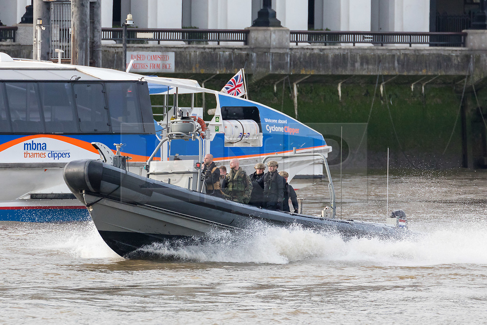© Licensed to London News Pictures. 23/10/2018. London, UK. Dutch Royal Netherlands Marines in a RIB travel past a Thames Clipper boat on the River Thames during a rehearsal for a display tomorrow when the Royal Marines and Royal Netherlands Marines will stage a joint on water capability demonstration with blank ammunition. As part of the Dutch state visit, King Willem-Alexander and Queen Máxima will attend the Dutch ship HNLMS Zeeland, which is anchored next to HMS Belfast. They will join The Duke of Kent on board and will be given a 10 minute display of the Royal Marines and Royal Netherlands Marines staging a joint on water capability demonstration.Photo credit: Vickie Flores/LNP