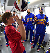 "Springdale Park Elementary School's George Smalley, left, shows off his basketball skills for Harlem Globetrotters' Jonathan ""Hawk"" Thomas and Brawley ""Cheese"" Chisholm, right, aboard the new Atlanta Streetcar while the team takes in downtown sights during a downtown tour on their day off Monday, March 9, 2015, in Atlanta. David Tulis / AJC Special"